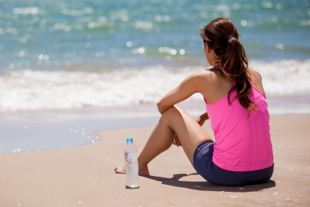 take a break: Young woman in sporty outfit taking a break to drink water after running at the beach Stock Photo