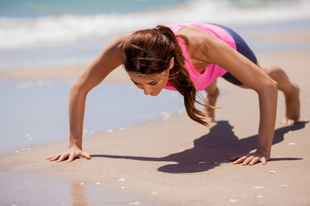 push: Young athletic brunette training and doing some push-ups at the beach Stock Photo