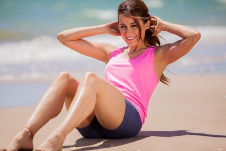 Cute young brunette doing some abs at the beach and smiling Stock Photo - 19932713