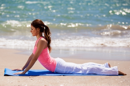 beach mat: Beautiful young brunette laying on a mat on the beach before doing some yoga