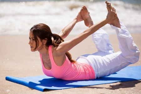 arching: Cute Hispanic brunette arching her back and holding her feet from behind in a yoga pose at the beach