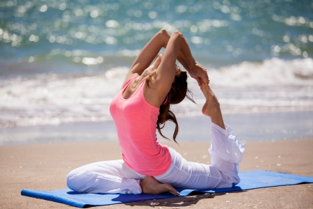 Pretty young brunette practicing some yoga at the beach
