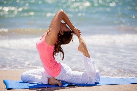 Cute young brunette practicing a few yoga poses on a sunny day at the beach photo