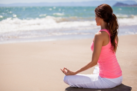Beautiful young woman doing some meditation and yoga at the beach photo