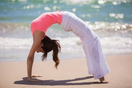 arching: Beautiful young woman arching her back and standing backwards on hands and feet while doing yoga at the beach Stock Photo