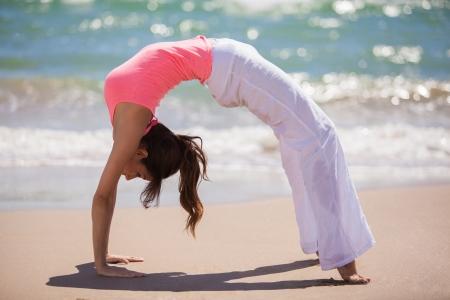 arching: Joven y bella mujer arqueando la espalda y se coloca al rev�s en las manos y los pies, mientras que hace yoga en la playa