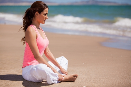 Beautiful young woman sitting at the beach and meditating photo