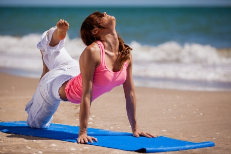 Gorgeous Hispanic woman trying a new yoga pose in the beach photo