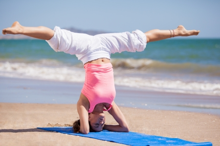 legs spread: Beautiful young woman standing on her head with her legs spread as part of a yoga pose at the beach