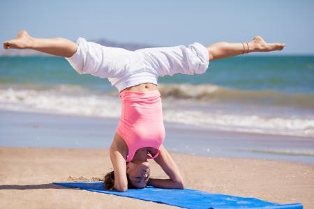 beine spreizen: Schöne junge Frau, die auf ihren Kopf mit ihren Beinen als Teil einer Yoga verteilt am Strand posieren Lizenzfreie Bilder