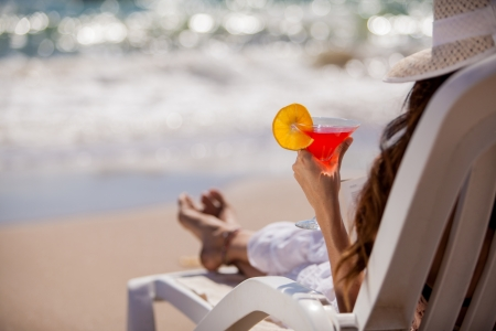 beach chairs: Closeup of a young woman relaxing at the beach with a cold martini Stock Photo