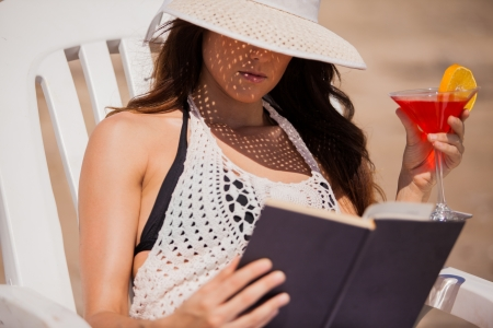 Pretty Hispanic young woman reading a book and drinking a martini at the beach photo