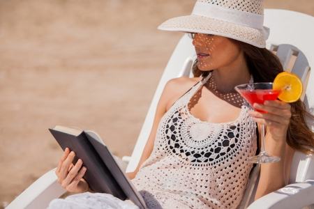 Relaxed young woman reading a book and drinking cocktails on her beach vacation photo