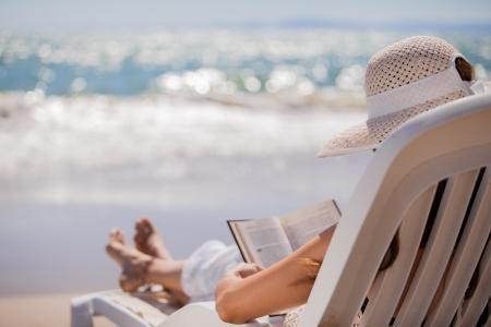 mujer leyendo libro: Mujer joven en vacaciones de relax en una silla frente al mar mientras se lee un libro