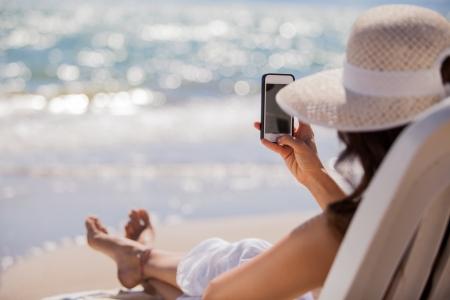 celulas humanas: Mujer joven compartir una foto de sus vacaciones en la playa en una red social