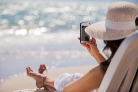 woman on phone: Young woman sharing a picture of her vacations on the beach on a social network