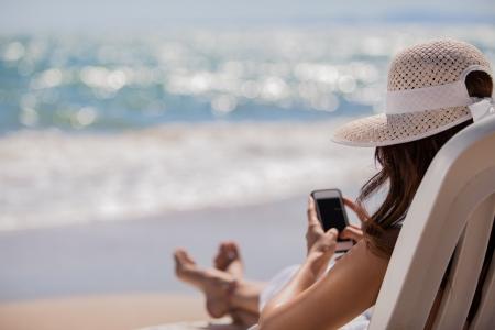 strandstoel: Jonge vrouw haar sociale netwerk status bijwerken terwijl ontspannen op het strand Stockfoto