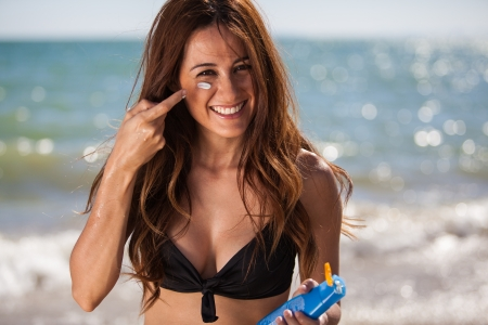 sunblock: Beautiful Hispanic woman putting some sunblock in her face and smiling