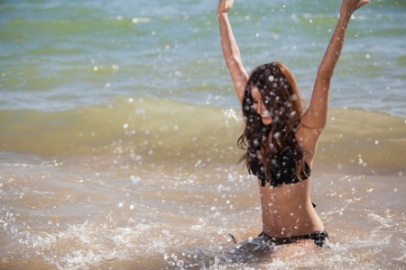 Happy young woman splashing some water and having fun at the beach Stok Fotoğraf