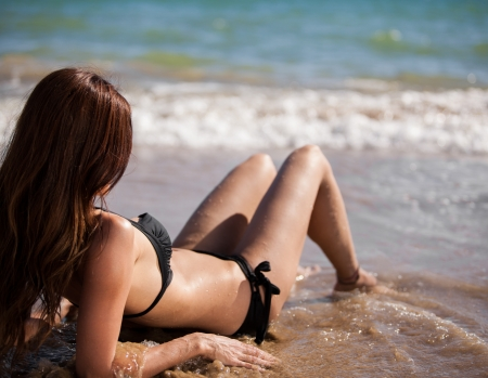 point of view: Sexy brunette wearing a bikini and sunbathing at the beach