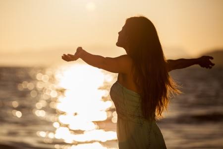 arms wide: Piuttosto giovane donna godendo di un tramonto sulla spiaggia con le braccia aperte Archivio Fotografico