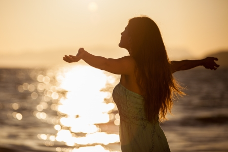 arms wide open: Pretty young woman enjoying a sunset at the beach with arms wide open Stock Photo