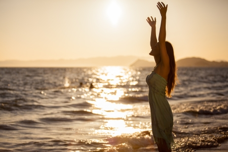 Young woman raising her arms towards the sky while looking at a beautiful sunset at the beach Stock Photo