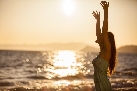 Happy young woman reaching for the sun and feeling free at the beach photo