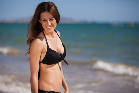 Cute happy brunette on a bikini relaxing at the beach photo