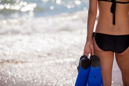 Young woman on a bikini holding a pair of flippers and shot from the back with copy space photo