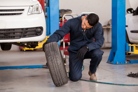Young mechanic inspecting a car tire at an auto shop Imagens