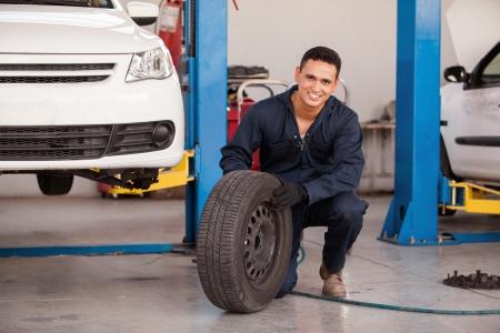mecanico automotriz: Mec�nico joven hermoso que quita un neum�tico de un coche en un taller mec�nico y sonriente Foto de archivo