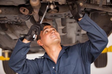 mecanico automotriz: Joven mecánico América trabaja en un coche suspendido en un taller mecánico