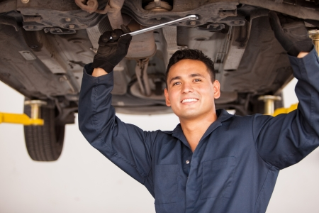 Portrait of a handsome young mechanic working on a suspended car at an auto shop and smiling