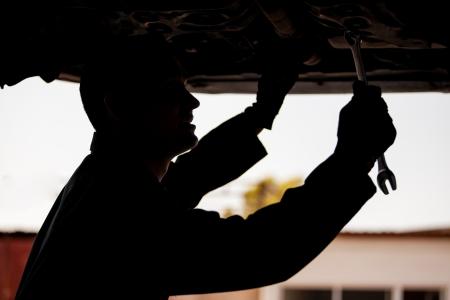 자동 가게에서 일시 중단 된 차량을 작업 젊은 정비공의 실루엣 스톡 콘텐츠