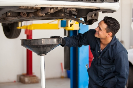 Happy young mechanic changing the oil of a car at an auto shop photo