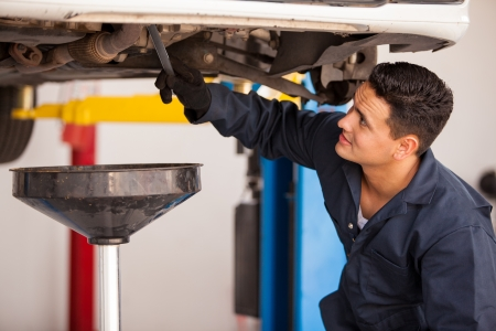 car repair shop: Young Hispanic mechanic draining engine oil from a car for an oil change at an auto shop