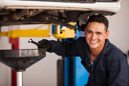 Gelukkig jonge monteur aftappen motorolie bij een auto-shop voor een olieverversing Stockfoto