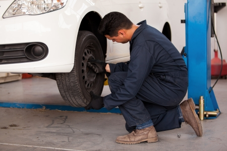 tire repair shop: Young mechanic rotating tires of a suspended car at an auto shop