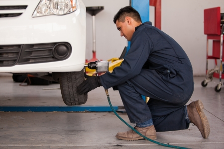 Young mechanic using an air gun to tighten a tire bolts on a suspended car at an auto shop photo