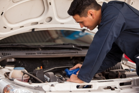 Young Latin mechanic pouring down new motor oil into a car s engine at an auto shop