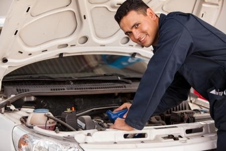 mecanico automotriz: Mecánico de joven feliz vertiendo un poco de aceite nuevo en el motor de un coche s en un taller mecánico