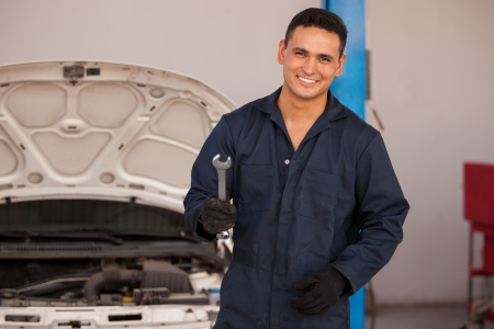 mechanic: Handsome young mechanic wearing an overall and smiling while holding a wrench