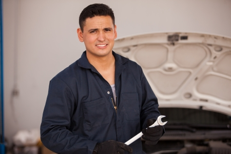 Portrait of a young Hispanic mechanic holding a wrench at an auto shop Stock Photo
