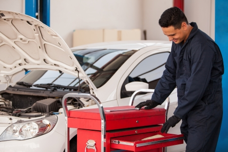adequate: Happy mechanic searching for an adequate tool to work on a car at an auto shop
