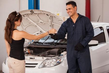 mecanico automotriz: Amistoso mecánico recibir un coche y las llaves del coche de un cliente femenino en un taller mecánico