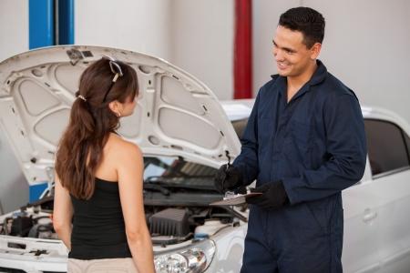 mecanico automotriz: Mecánico joven hermoso recibir un coche en un taller mecánico de una clienta y sonriente