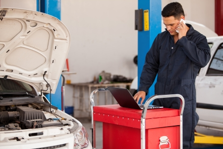 Handsome young mechanic talking to a customer on a cellphone while working on a computer at an auto shop