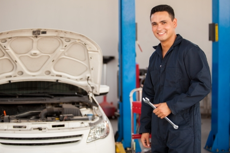 Handsome Hispanic mechanic enjoying his work at an auto shop and smiling Archivio Fotografico