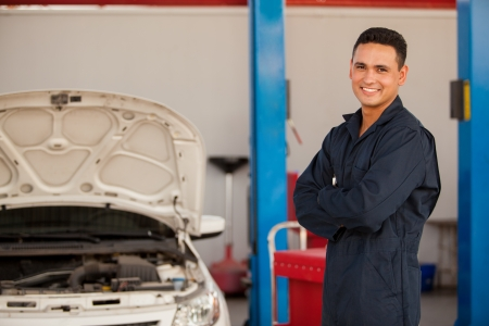 auto repair: Young mechanic working at an auto shop and smiling